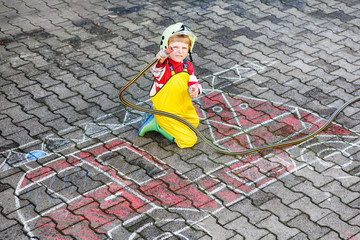Funny little child of four years having fun with fire truck pict