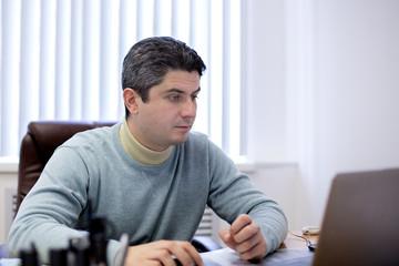Молодой человек смотрит на экран монитора