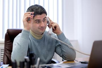 Молодой человек говорит по телефону в офисе