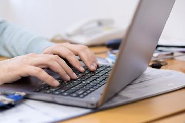 Руки человека, печатающего на компьютере