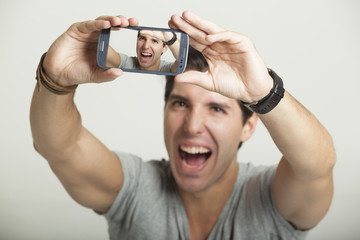 young attractive man taking pictures of him self with phone
