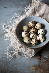 quail eggs on bowl on rustic table with frayed cloth