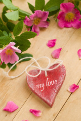 Wooden heart with roses on wood background