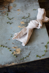 knotted towel on rustic blue scraped wooden table with thyme