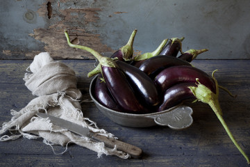 group of long eggplants on plate on wooden table with cloth
