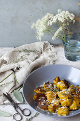 homemade pumpkin dumplings on table with flowers and scissor