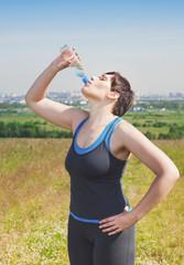 Beautiful fitness plus size woman drinking water