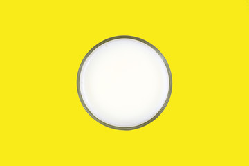 Glass of skim milk on a yellow background