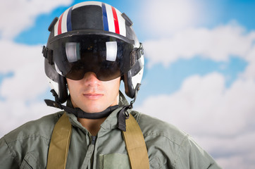 portrait of young pilot wearing helmet with a sky background