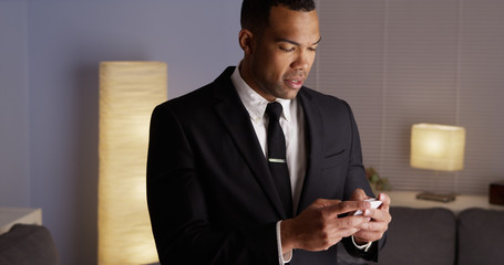 Handsome black businessman typing on smartphone