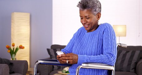 Mature black woman laughing and texting