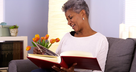 Mature Black woman looking through photo album
