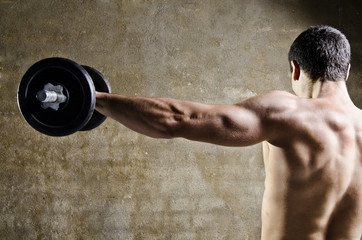 Man lifting weights with shoulders training at old gym
