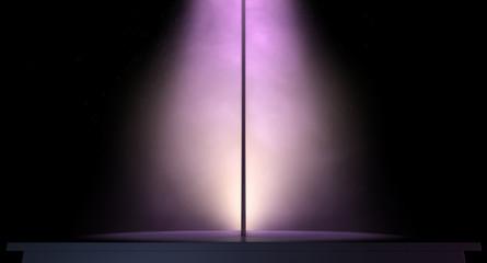 stripper pole on a stage lit by a single spotlight
