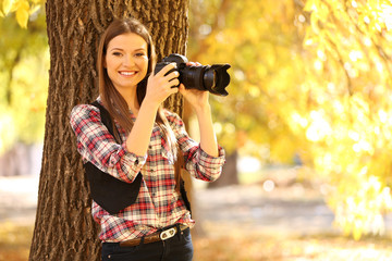 Beautiful young photography take photos outdoors in park