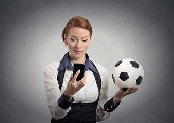 businesswoman looking on smartphone watching football game