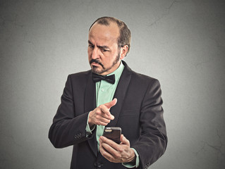 angry middle aged business man looking on mobile phone