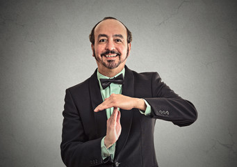 Businessman showing time out sign hand gesture on grey
