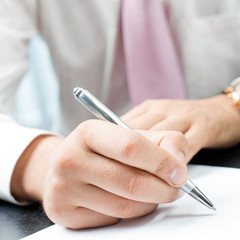 Closeup of writing businessman with document