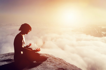 Asian man meditates in yoga position in mountains at sunset