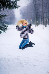 beautiful young blond woman in a winter park. Snow-covered trees