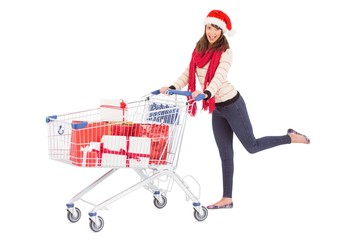 Cute woman in santa hat with shopping trolley