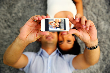 Couple making selfie photo on smartphone. Focus on smartphone