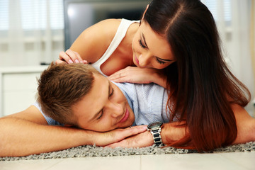 Young beautiful couple relaxing on the floor at home