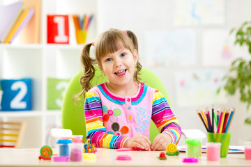 Little child playing with colorful clay
