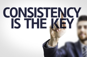 Business man pointing the text: Consistency is The Key