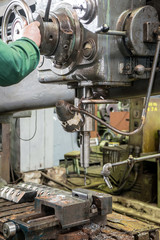 machinist working on industrial drilling machine in workshop