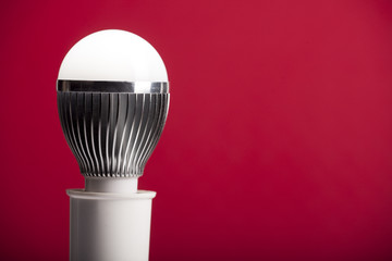 LED bulb in holder on red background