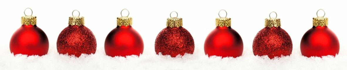 Christmas border of shiny red baubles resting in snow