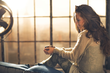 Young woman enjoying cup of coffee in loft apartment