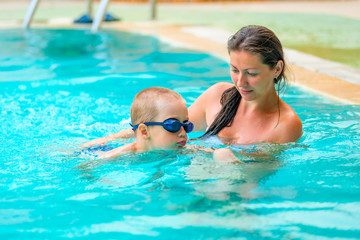 5 years old boy learning to swim with mom