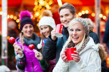 Freunde, Glühwein und Kandisäpfel auf Weihnachtsmarkt