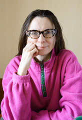 Portrait of a smiling mature woman with glasses wearing a pink pull-over at morning after breakfast