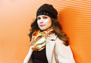 Portrait pretty woman in coat and hat against colorful wall outd