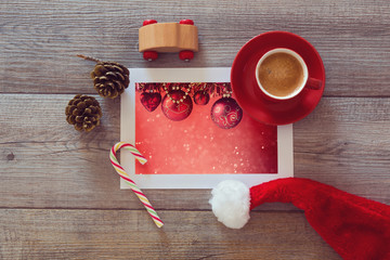 Photo of Christmas decorations with coffee and Santa hat.