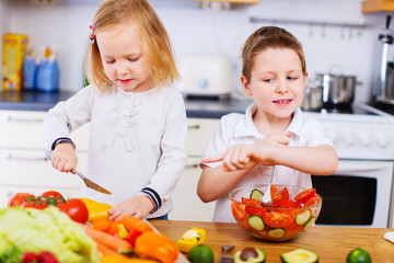 Two little kids making salad