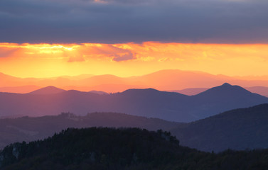 Fototapete - Sunset over color mountain silhouette.