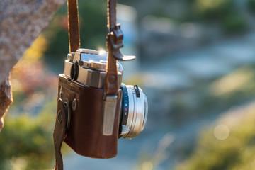 Vintage camera hangs on rock