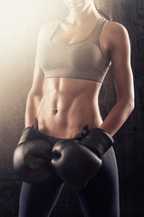 Athletic fitness woman with boxing gloves showing strong abs