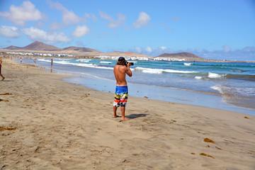 hombre caminando por la playa de famara en lanzarote