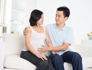 Asian couple. Husband and 8 months pregnant wife.