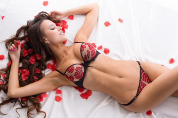 Gorgeous underwear model posing with rose petals