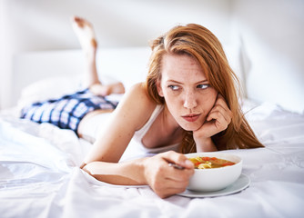 woman in bed eating chicken noodle soup while sick
