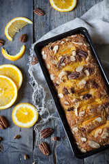citrus plumcake with pecan walnuts on mold with orange slices
