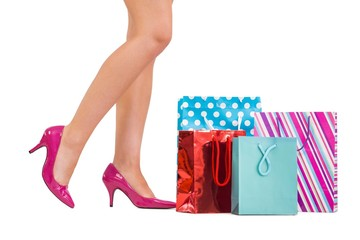 Womans legs in high heels with shopping bags