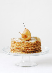 Fried pancakes on a glass stand with roasted pears.